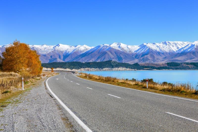Strada scenica lungo il lago Tekapo alla bella mattina soleggiata Il lago Tekapo e le montagne con neve in autunno, Canterbury, s fotografia stock libera da diritti
