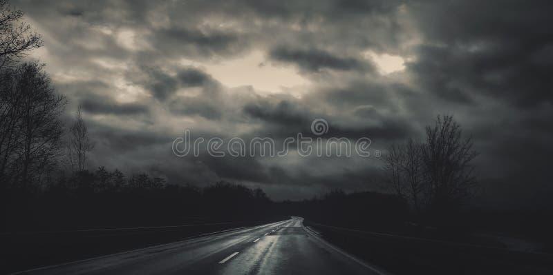 Strada scura sul giorno di Natale con il cielo nuvoloso fotografia stock