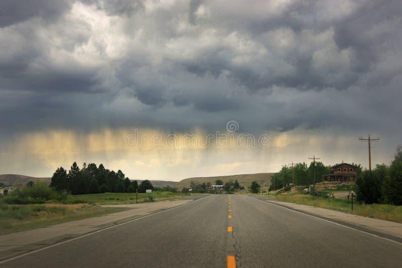 Strada sola con threatning le nuvole di pioggia scure immagini stock