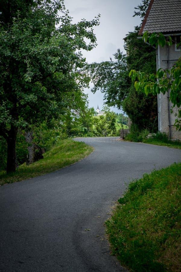 Strada stradale asfaltata d'avvolgimento che conduce alla chiesa sulla collina immagini stock
