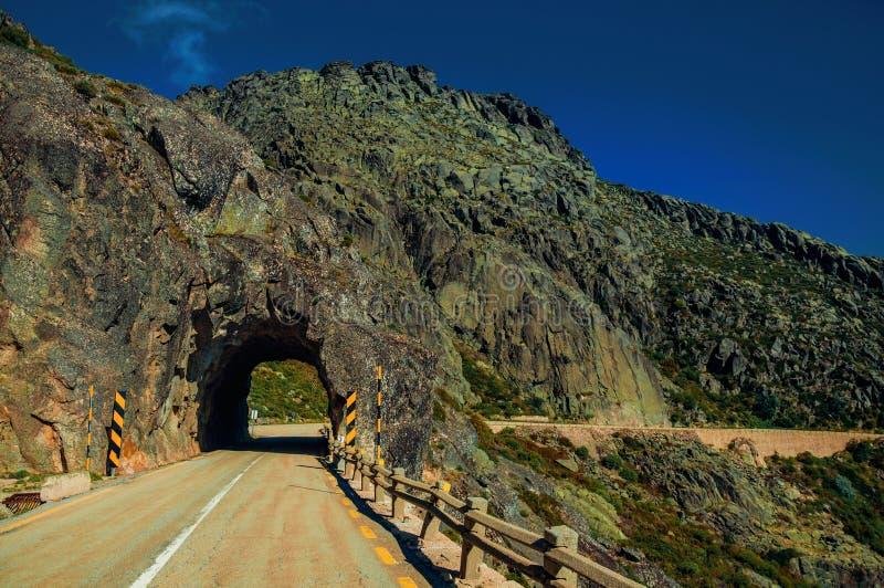 Strada su paesaggio roccioso che passa tramite il tunnel fotografie stock libere da diritti