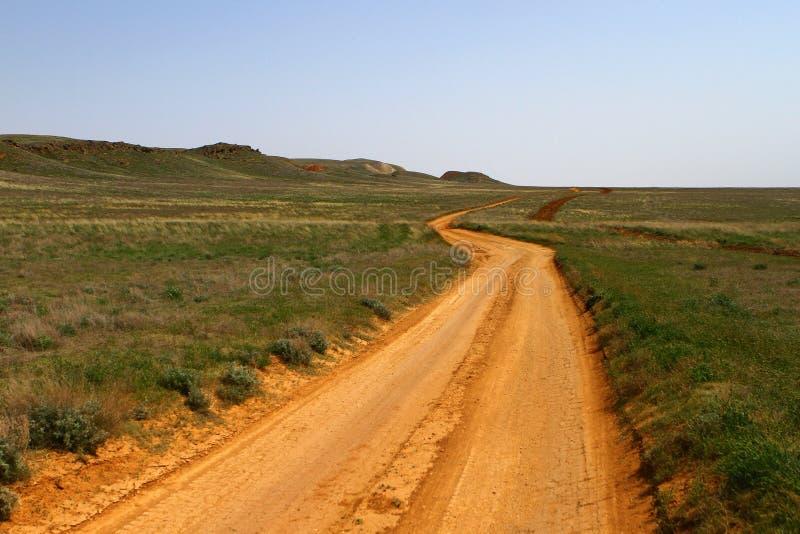 Strada a terra nella steppa con le montagne fotografia stock