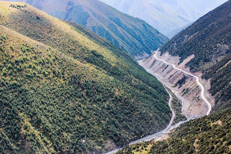 Strada tortuosa della montagna nella valle verde fotografie stock
