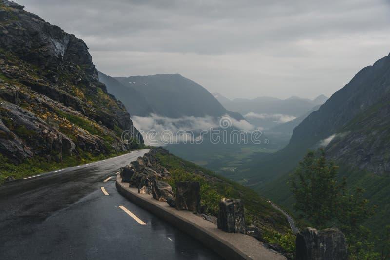 Strada tortuosa nelle montagne della Norvegia, Trollstigen, scala del troll, tempo triste triste, asfalto bagnato immagine stock
