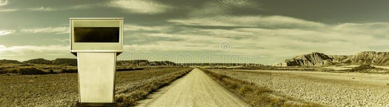 Strada in un paesaggio del deserto con la pompa di benzina fotografia stock libera da diritti