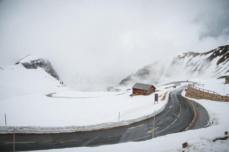 Strada vuota che conduce attraverso la campagna, la neve & la nebbia sceniche alla montagna di Grossglockner, Austria fotografie stock