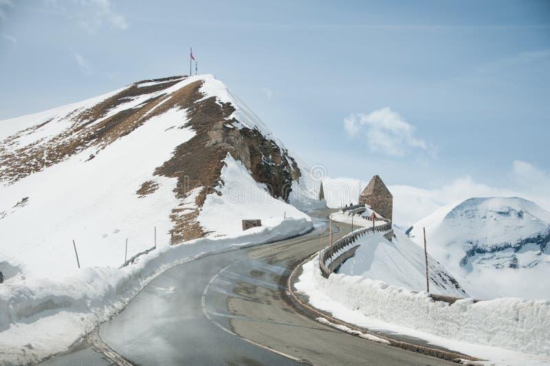 Strada vuota che conduce attraverso la campagna, la neve & la nebbia sceniche alla montagna di Grossglockner, Austria immagine stock