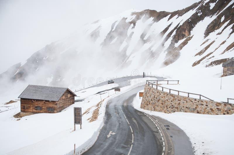 Strada vuota che conduce attraverso la campagna, la neve & la nebbia sceniche alla montagna di Grossglockner, Austria fotografia stock libera da diritti