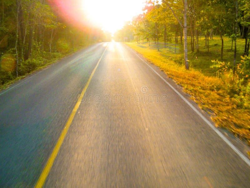 Strada vuota con luce solare in cielo arancio profondo sopra la strada asfaltata con leggero mosso fotografie stock libere da diritti