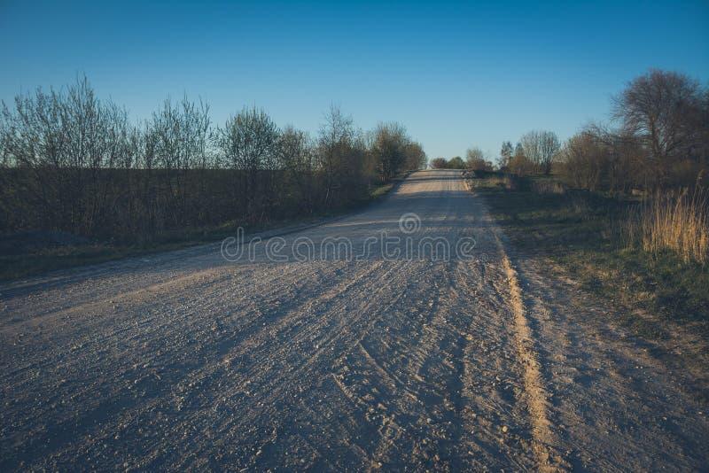 Strada vuota della ghiaia in campagna nella prospettiva con gli alberi in Unione Sovietica fotografia stock libera da diritti
