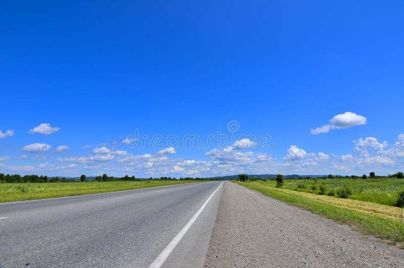 Strada vuota diritta che corre all'orizzonte fotografia stock