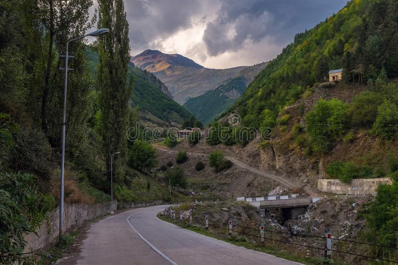 Strada vuota in montagne di Svaneti Georgia con immondizia sotto il ponte immagini stock libere da diritti