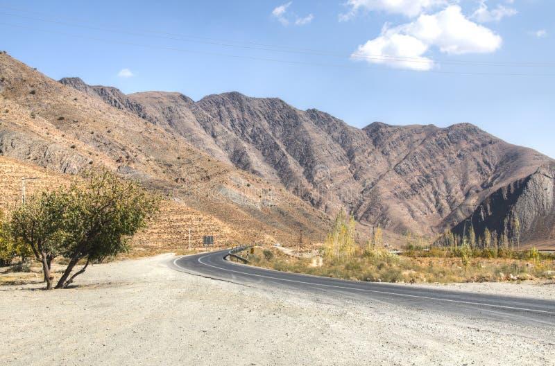 Strada vuota verso il deserto di Dasht-e Lut, Iran fotografie stock libere da diritti