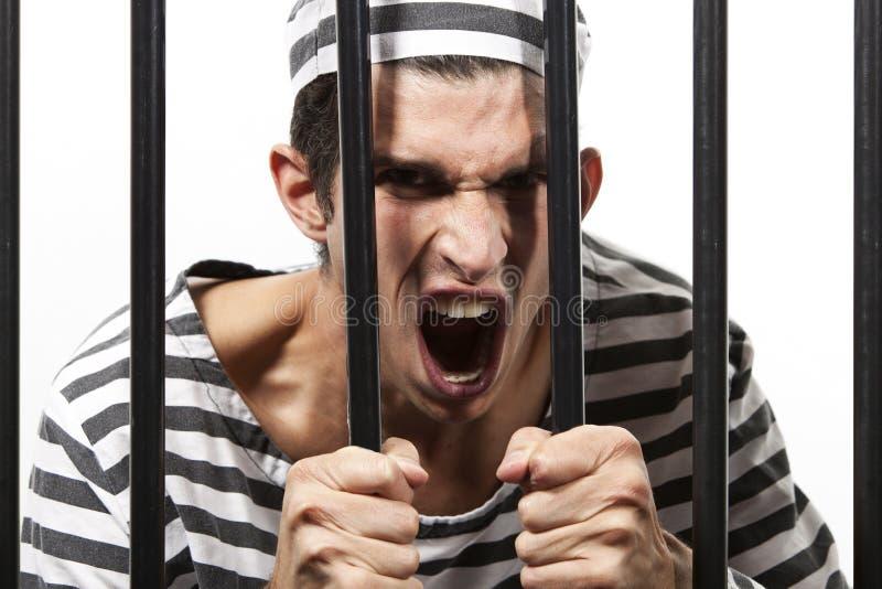 Straffången skriker till och med fängelsestänger arkivbild
