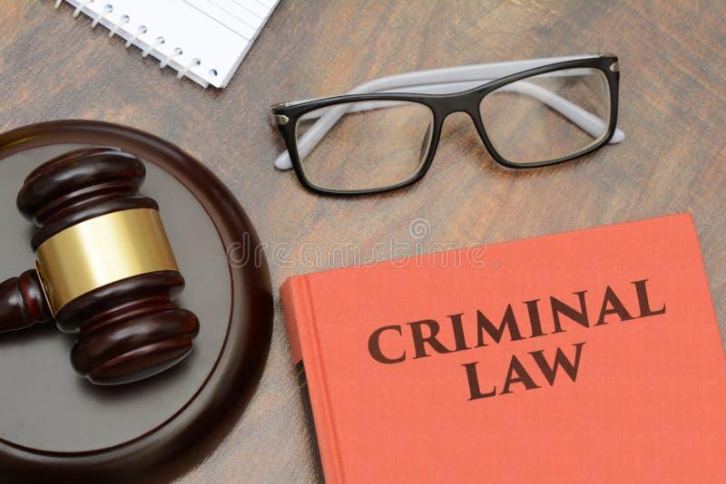 Strafrechtteken met houten hamer en rood boek stock afbeeldingen