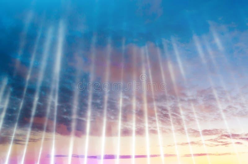 Strahlen des Lichtes von einer künstlichen Lichtquelle zeigend oben in den Himmel bei den Wolken und dem Sonnenuntergang lizenzfreie stockfotos