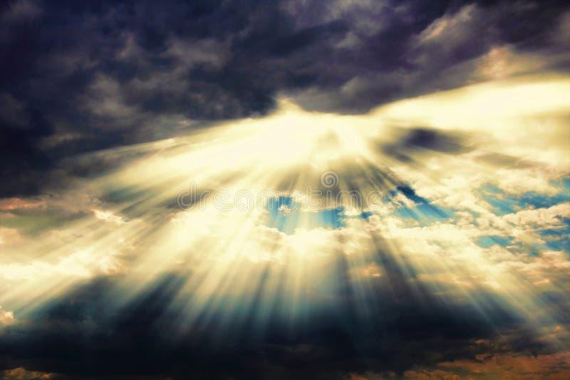 Strahlen des Sonnenlichts kommend durch drastische Wolken stockbilder