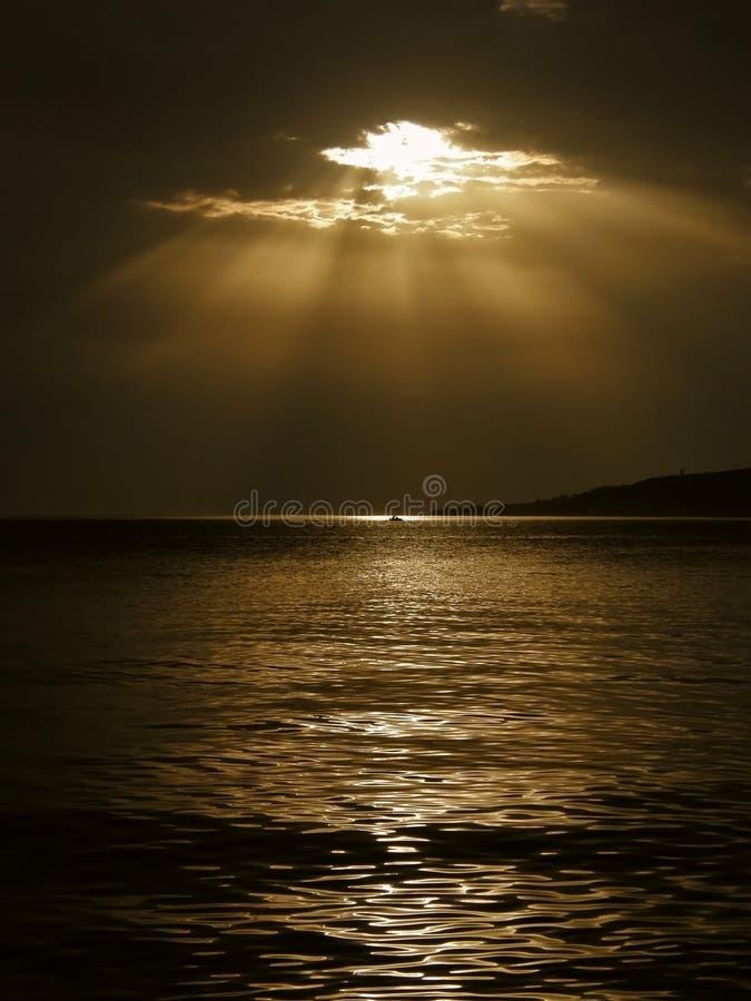 Strahlen und ein Boot des Gottes auf dem Meer lizenzfreie stockfotografie