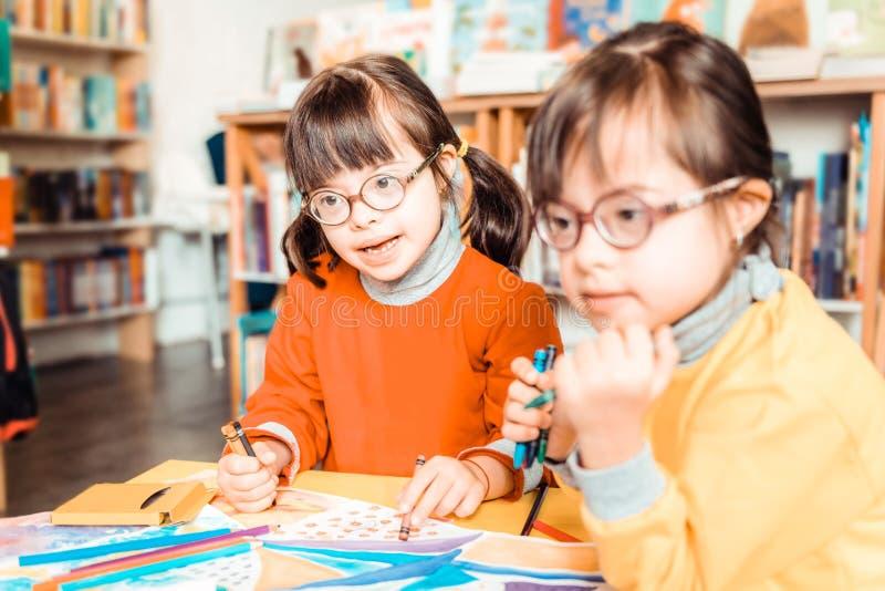 Strahlende Kleinkinder mit aufmerksam schauendem Down-Syndrom lizenzfreies stockfoto