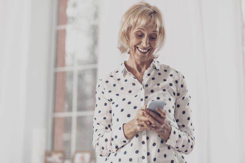 Strahlende lächelnde Dame beim Ablesen der reizenden Mitteilung stockbilder
