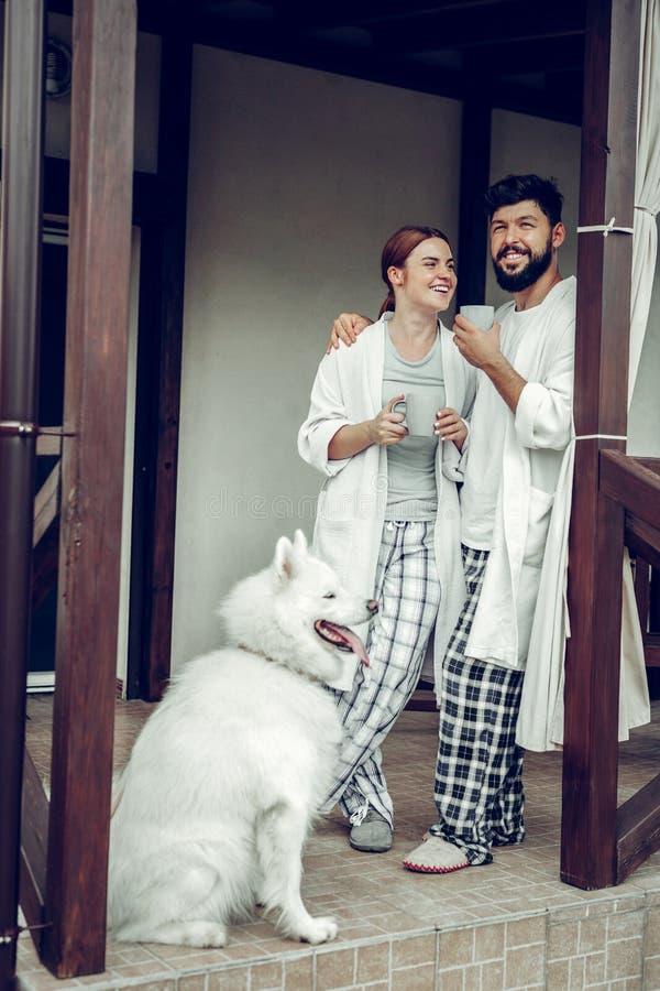 Strahlende lächelnde glückliche Mittelerwachsengatten, die nahe Türen mit Kaffee stehen lizenzfreie stockfotos
