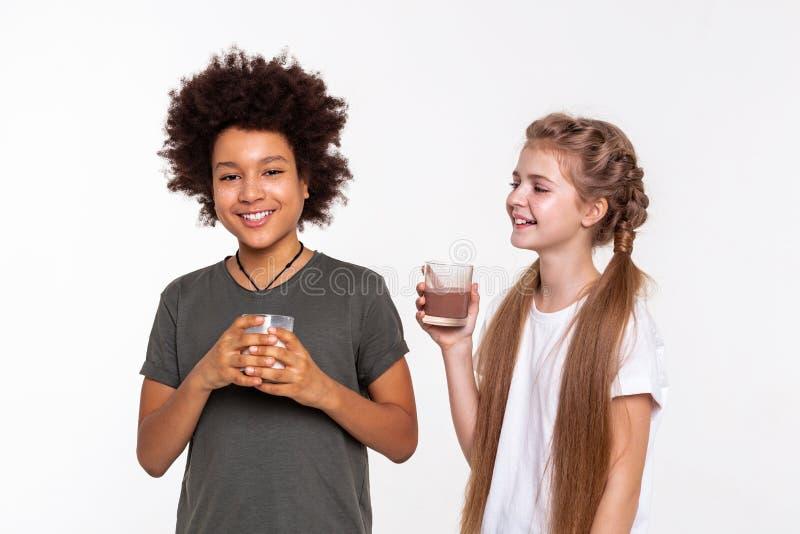 Strahlende positive Kinder, die Gespräch beim Trinken haben lizenzfreie stockbilder