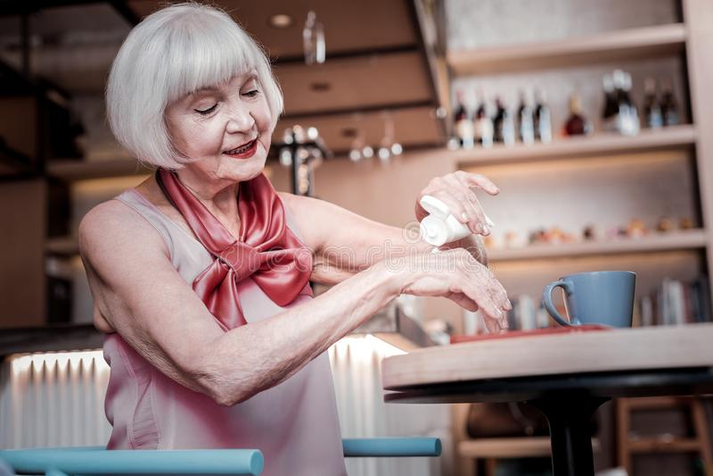 Strahlende schöne ältere Frau, die in einem Café und in einer Behandlung stillsteht stockfotos