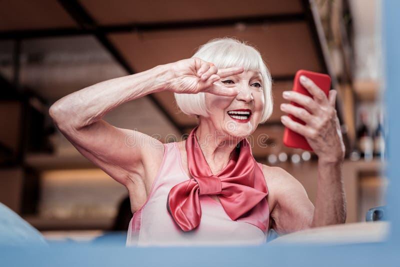 Strahlende schöne Blondine, die während des Videoschwätzchens aufwerfen stockfoto