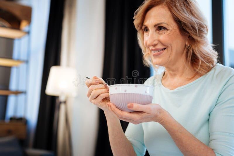 Strahlende schöne Dame, die sorgfältig keramische Schüssel hält stockfotografie