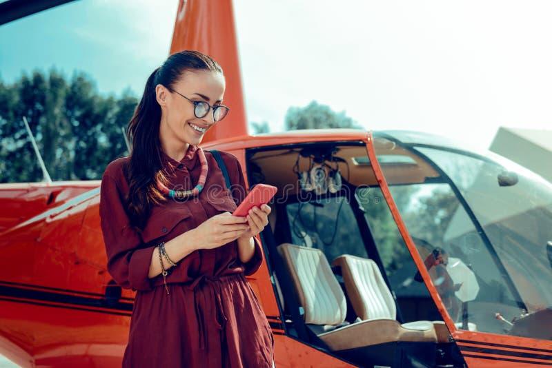 Strahlende sch?ne Dame im Klarglas, das mit ihrem Smartphone zufriedengestellt wird lizenzfreie stockfotografie