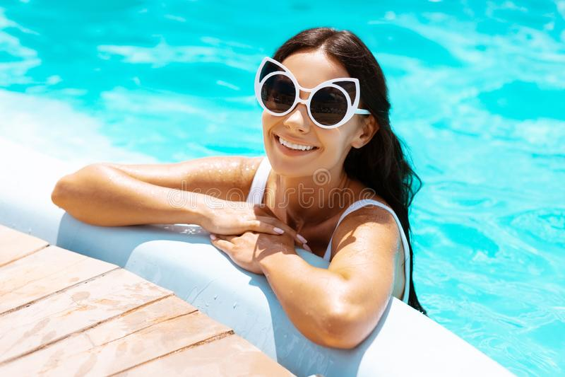 Strahlende tragende Sonnenbrille der Frau, die im Pool kühlt stockfotografie