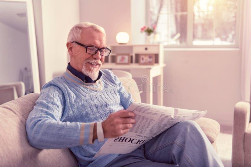 Strahlender Pensionär, der den Spaß liest Morgenzeitung hat lizenzfreie stockbilder
