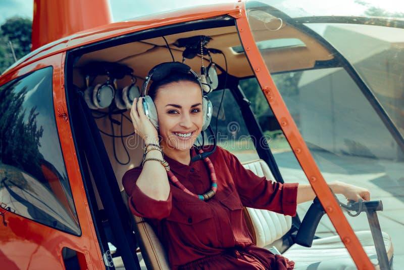 Strahlender schöner Pilot mit dem breiten Lächeln, das ihre Berufskopfhörer hält stockbild