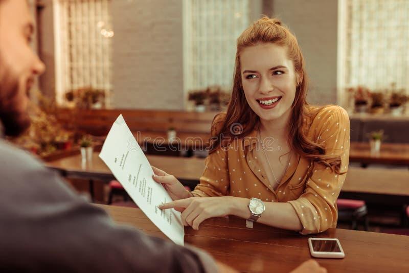 Strahlendes Mädchen, das auf das Menü sitzt am Stangenzähler zeigt stockbilder