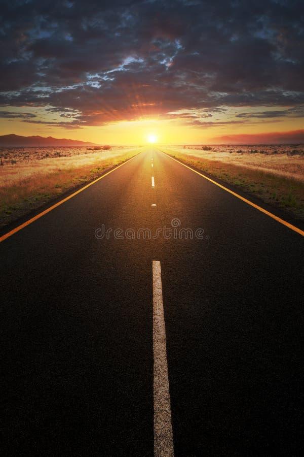 Straight asphalt road leading into sunlight stock images