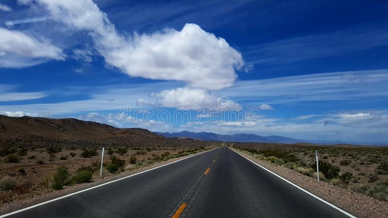 Straight road through Death Valley. A straight empty road through Death Valley, California stock photos