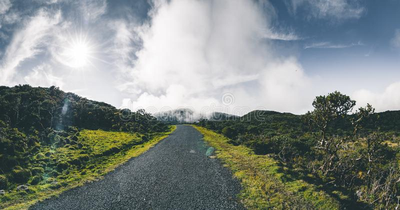Straight EN3 longitudinal road northeast of Mount Pico and the silhouette of the Mount Pico along , Pico island, Azores. Portugal. Photo taken in Azores royalty free stock image