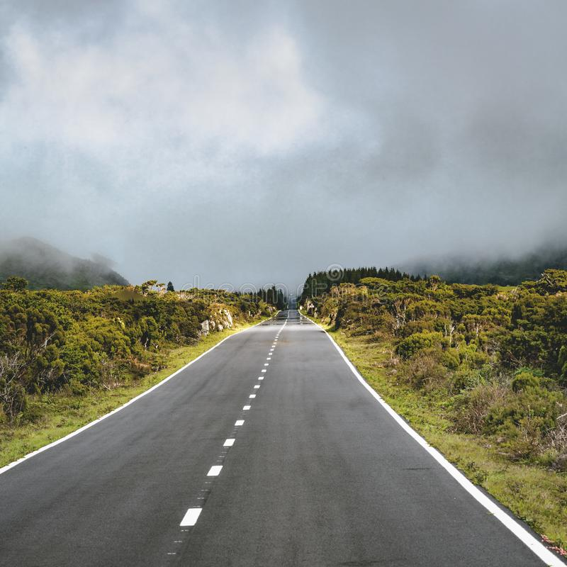 Straight EN3 longitudinal road northeast of Mount Pico and the silhouette of the Mount Pico along , Pico island, Azores. Portugal. Photo taken in Azores stock photography