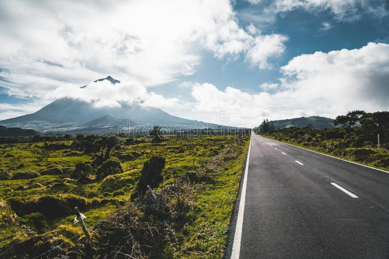 Straight EN3 longitudinal road northeast of Mount Pico and the silhouette of the Mount Pico along , Pico island, Azores. Portugal. Photo taken in Azores stock image
