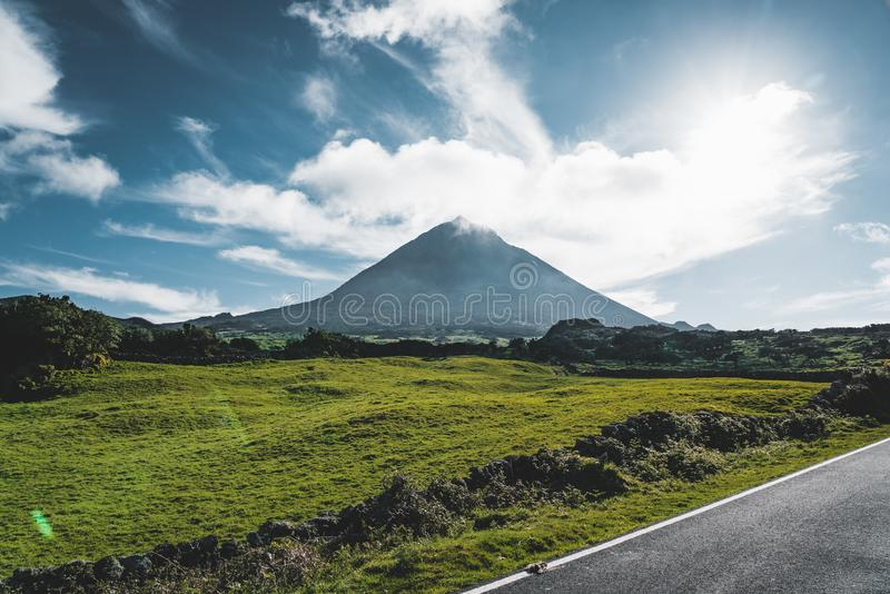 Straight EN3 longitudinal road northeast of Mount Pico and the silhouette of the Mount Pico along , Pico island, Azores. Portugal. Photo taken in Azores royalty free stock photography