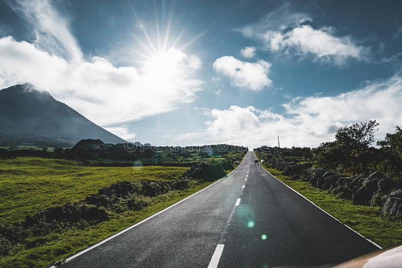 Straight EN3 longitudinal road northeast of Mount Pico and the silhouette of the Mount Pico along , Pico island, Azores. Portugal. Photo taken in Azores royalty free stock photo