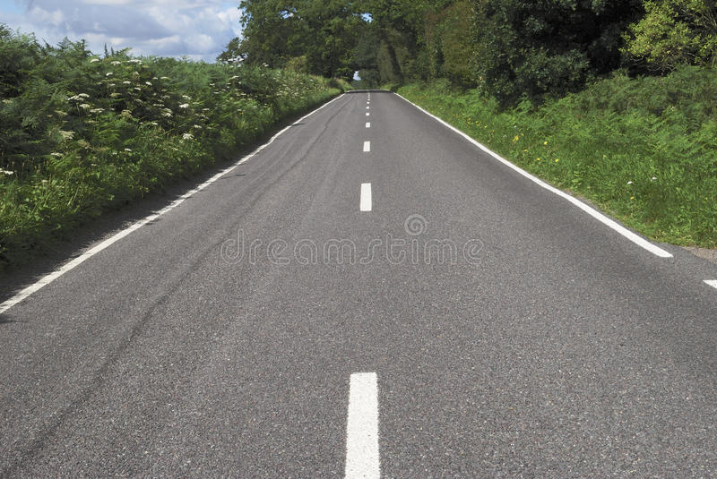 Straight English country road. Straight tarmac country road with white lines on edge of woodland in West Sussex. England stock image