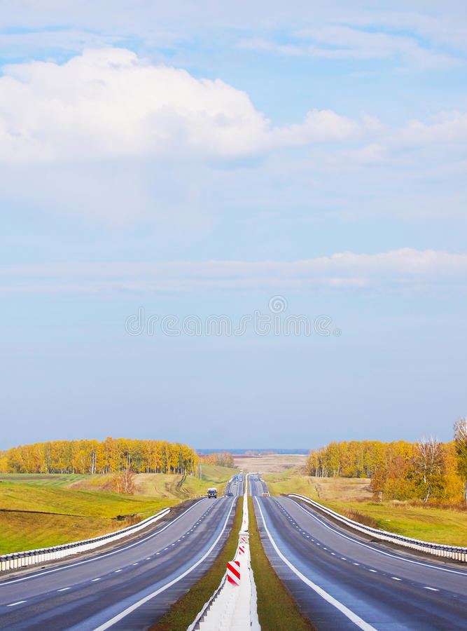 Straight highway among autumn fields in the sunny day stock photos