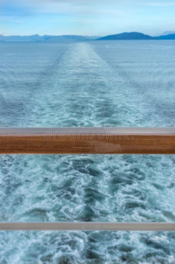 Straight line of ship`s wake and wooden railing at stern. Straight line of ship`s wake and stern railing. South facing view of Dixon Entrance, Inside Passage royalty free stock photography
