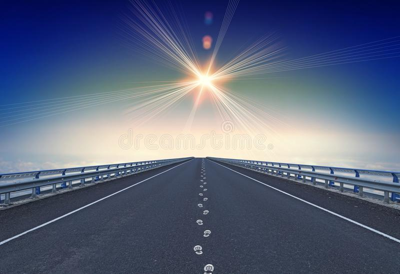Straight motorway with footprints and a lodestar over horizon stock photos