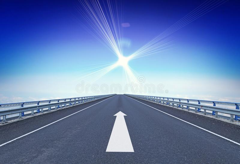Straight motorway with a forward arrow and guiding star over horizon stock image
