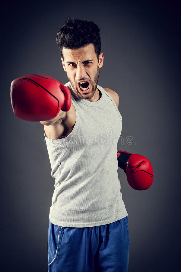 Straight punch. Boxer is giving a straight punch while screaming royalty free stock photo