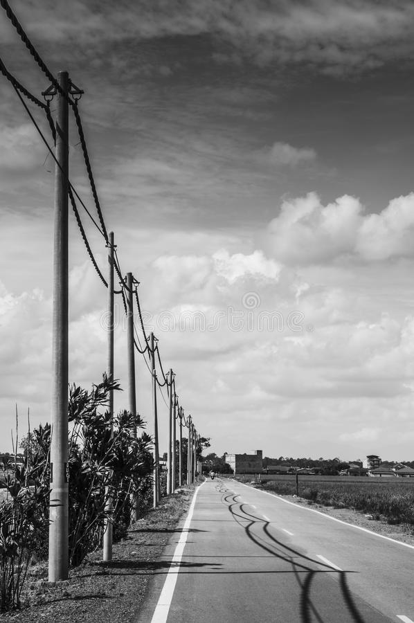 Straight road. Electric cables and poles along a straight tarmac road in black and white royalty free stock images