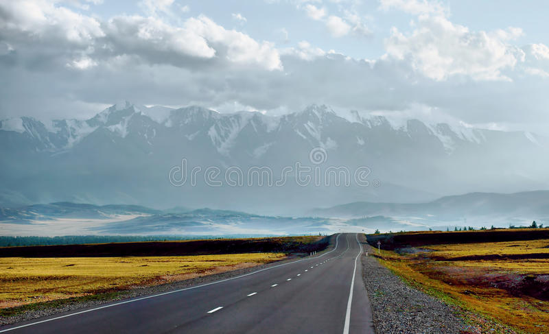 Straight road going through the valley to mountains stock image