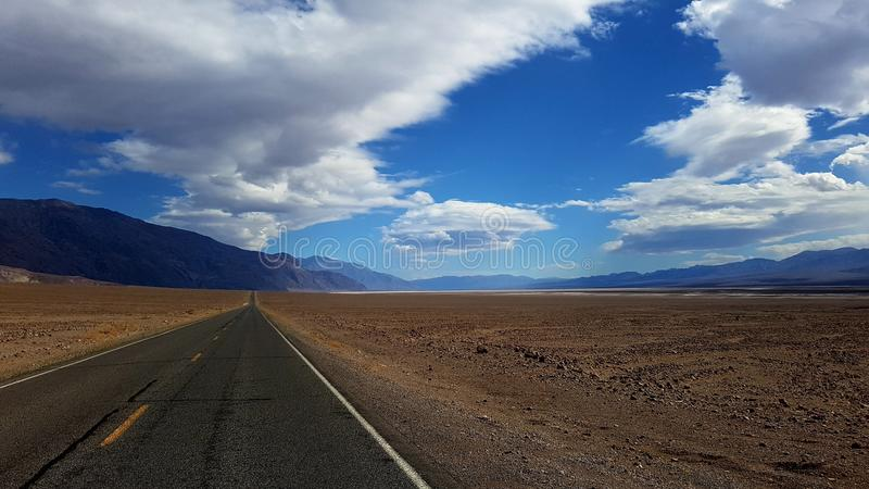 Straight road in Death Valley. A straight road and mountains in the background, Death Valley, California royalty free stock photo